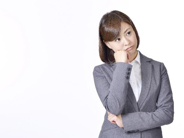 腕を組むスーツスタイルの女性